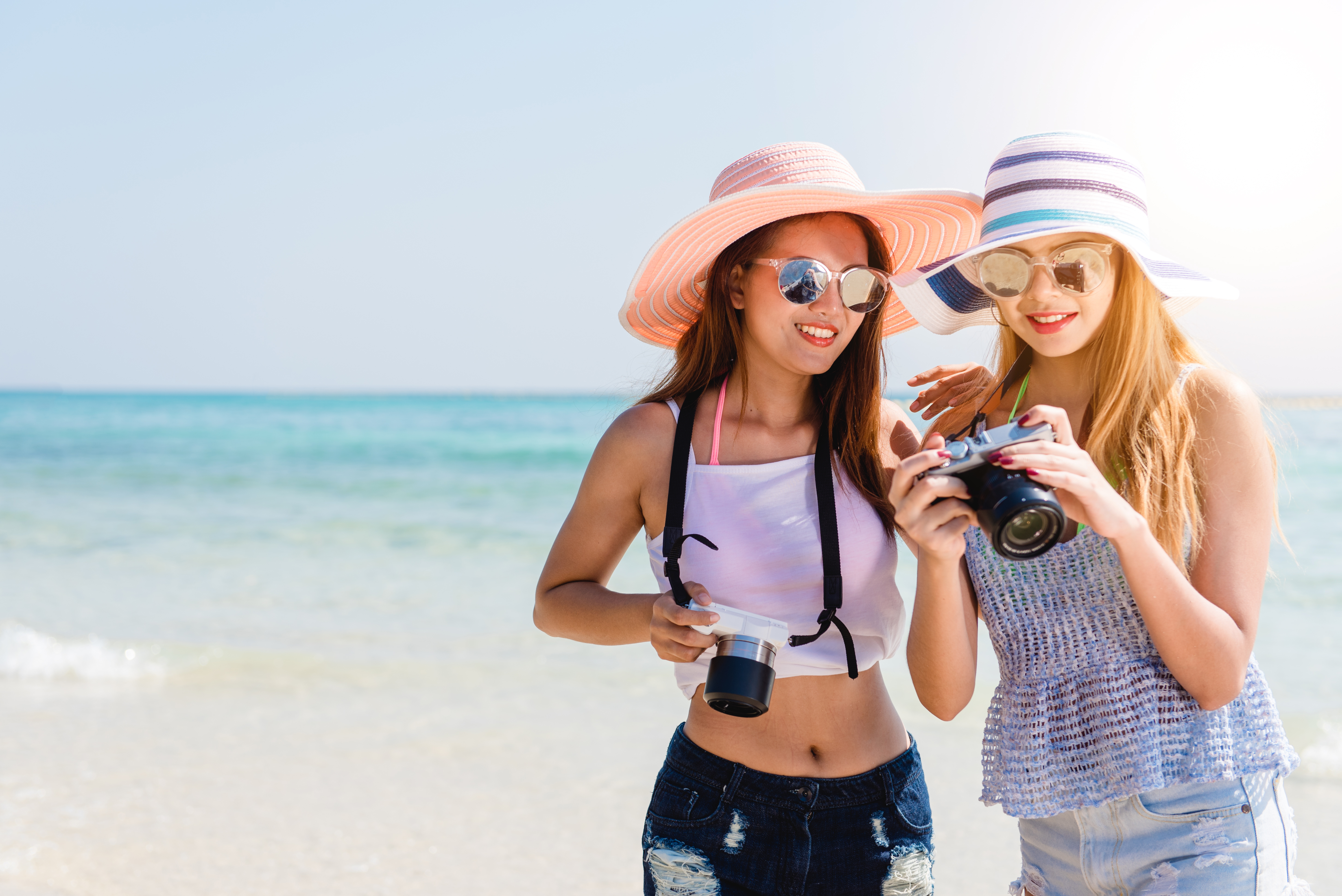 Two cool trendy hipster girls at the beach enjoying vacation on