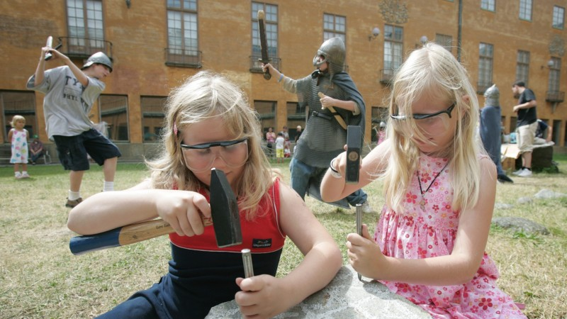 Two girls carve runes on the yard of the Museum of History in Stockholm.