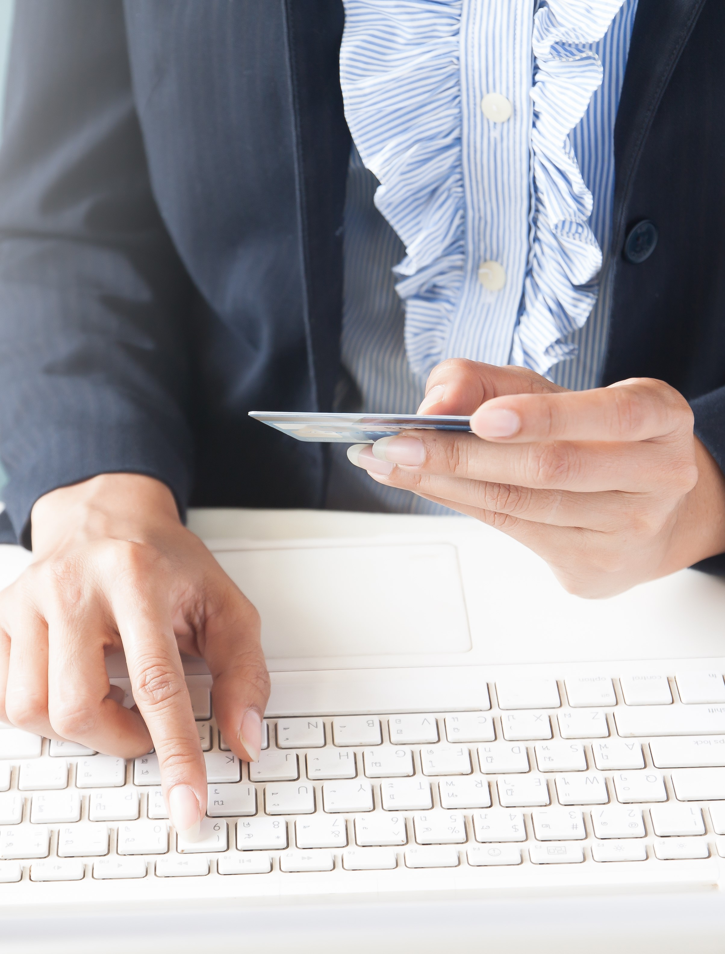 Business woman in dark suit holding credit card and using laptop