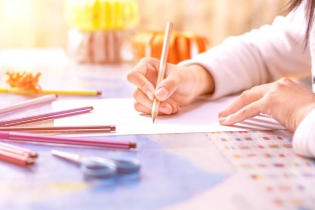 close-up-of-schoolgirl-writing_1127-324
