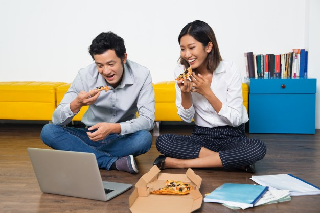 happy-asian-couple-eating-pizza-looking-at-laptop_1262-959