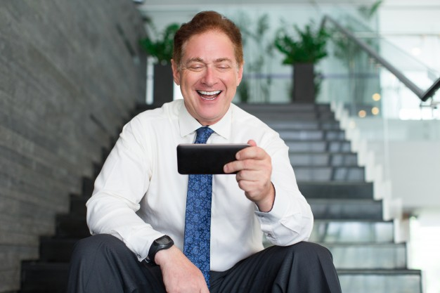 senior-businessman-laughing-at-internet-video_1262-3069