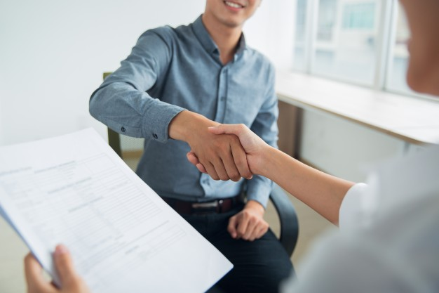smiling-asian-businessman-shaking-partners-hand_1262-2310