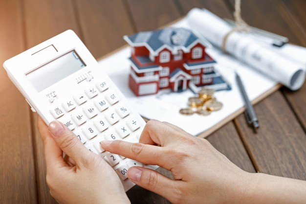 a-female-hand-operating-a-calculator-in-front-of-a-villa-house-model_1387-956