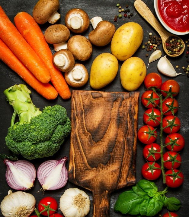 black-surface-with-vegetables-and-a-cutting-board_1309-39