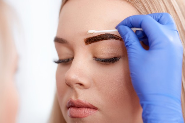 cleaning-face-of-client-during-permanent-make-up_1208-446