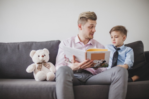father-sitting-with-his-son-on-the-sofa-and-reading-a-story_23-2147624623