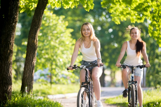 girls-riding-bike-and-smiling_1218-152