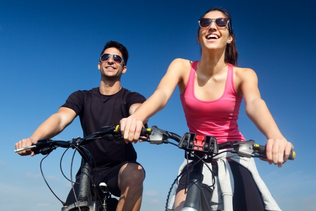 happy-young-couple-on-a-bike-ride-in-the-countryside_1301-6087