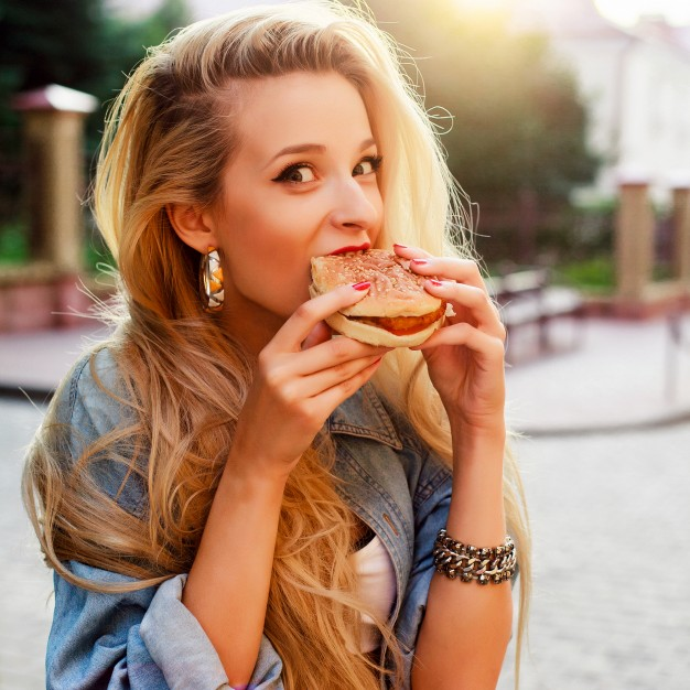 hungry-young-woman-eating-a-tasty-burger_1140-17