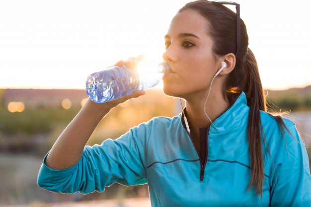 portrait-of-young-woman-drinking-water-after-running_1301-4186