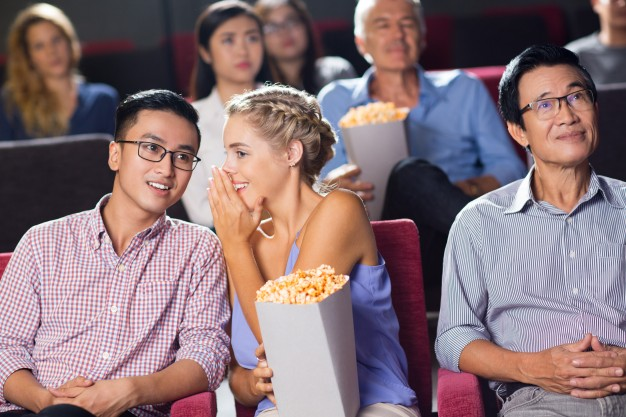 smiling-multiethnic-young-couple-sitting-in-cinema_1262-2432