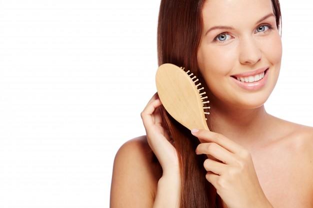 smiling-woman-brushing-her-healthy-hair_1098-4047