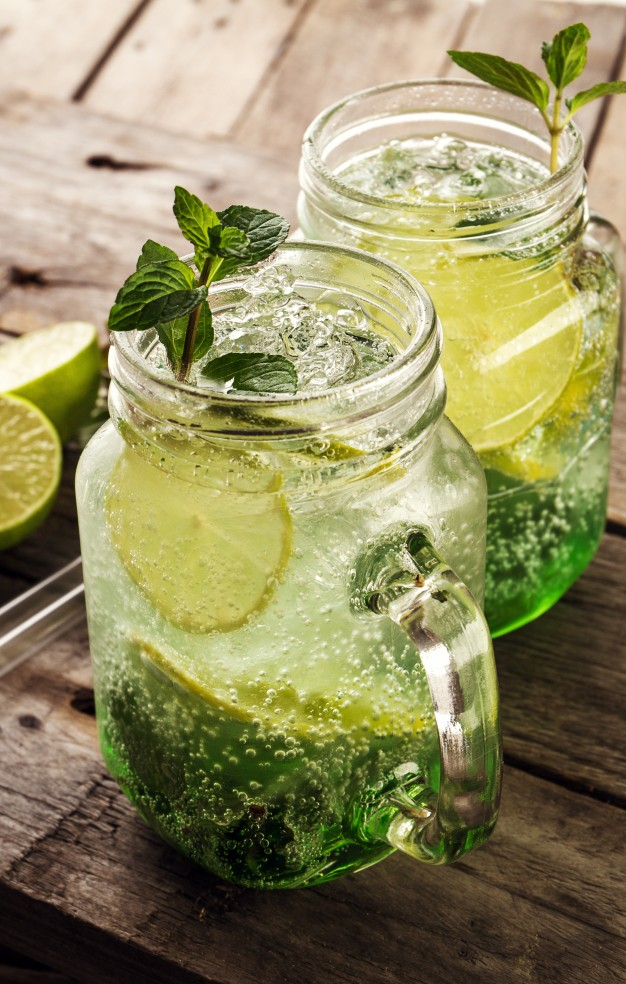 tasty-cold-fresh-drink-lemonade-with-lemon-mint-ice-and-lime-in-glass-on-wooden-table-closeup_1220-1340