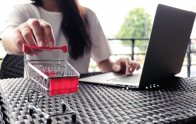 woman-and-small-shopping-cart-with-laptop-for-internet-online-shopping-concept_1715-1003