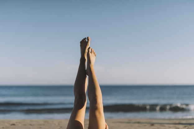 woman-stretching-legs-lying-at-the-beach_23-2147643636