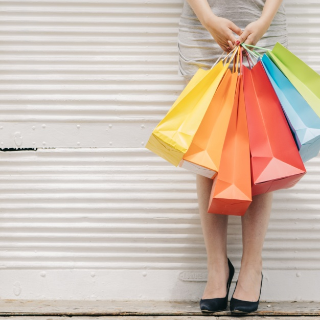 woman-with-colorful-bags-at-wall_23-2147666161