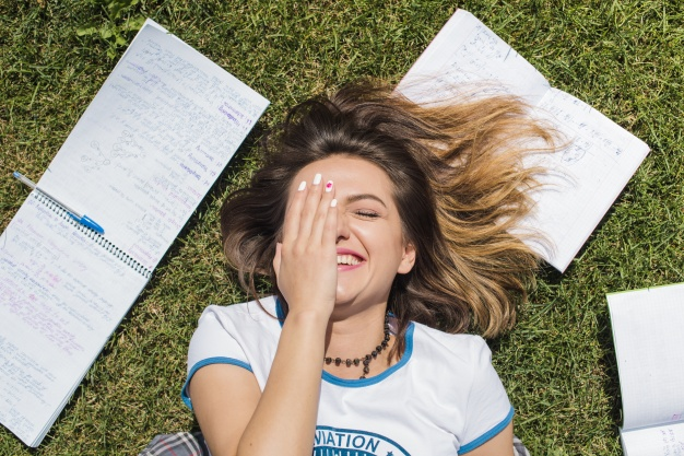 girl-lying-on-grass-smiling_23-2147657207