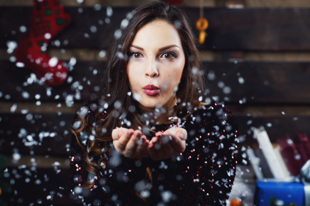 pretty-girl-blows-snow-from-her-palms-standing-in-room-prepared-for-christmas-holidays_1304-5632
