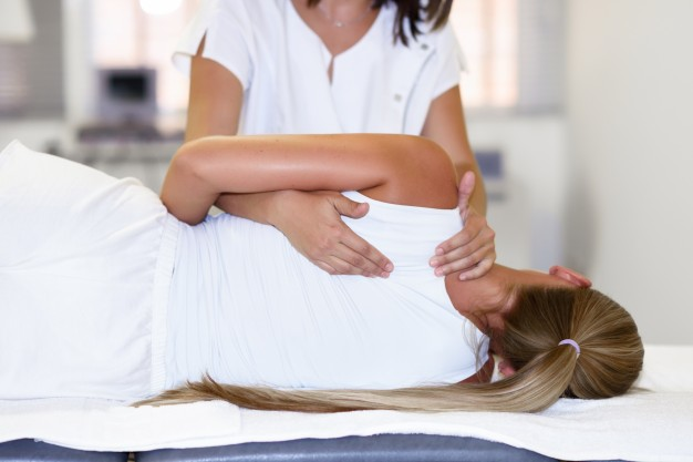 professional-female-physiotherapist-giving-shoulder-massage-to-blonde-woman_1139-1113