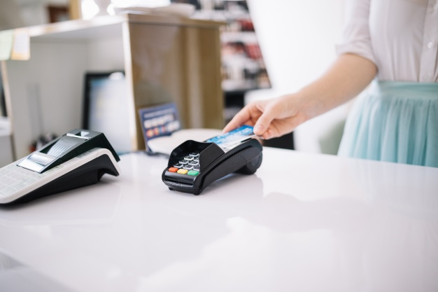 woman-using-payment-terminal-on-cashier-desk_23-2147688729