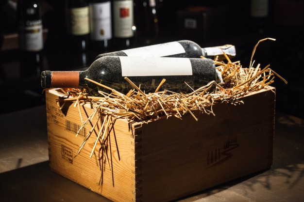 wooden-box-with-hay-and-bottles-of-wine-on-it_1304-2870