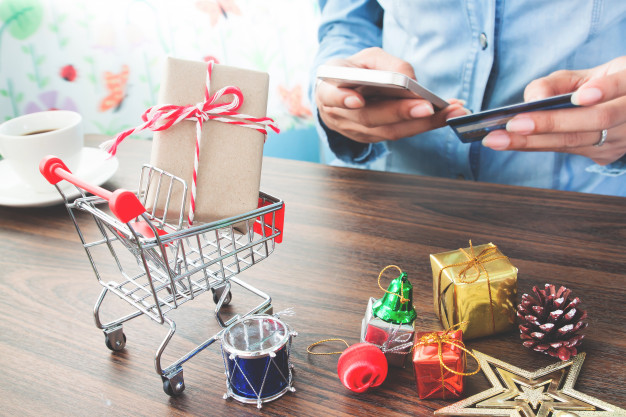 close-up-of-gift-box-and-christmas-decorations-in-shopping-cart-with-woman-hand-online-paying-in-background_1428-1174