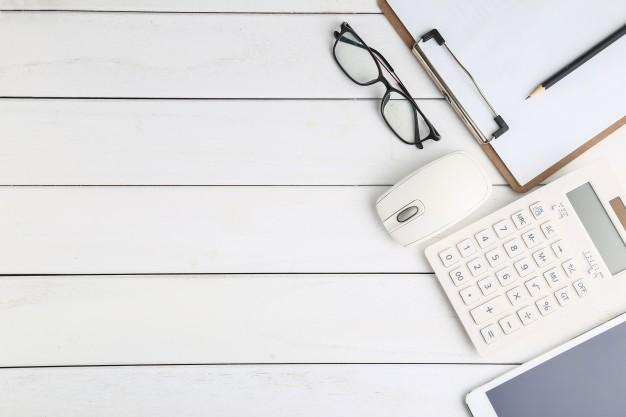 glasses-calculator-and-tablet-on-white-neat-desk_1387-387