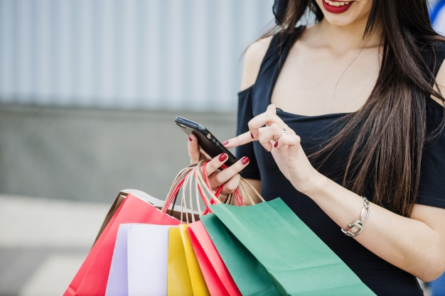 woman-with-shopping-bags-holding-smartphone_23-2147652181