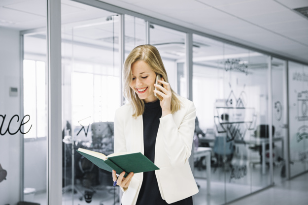 businesswoman-calling-and-looking-into-book_23-2147715588