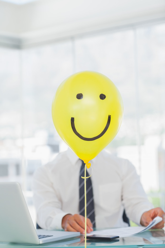 yellow-balloon-with-cheerful-face-hiding-businessmans-face_13339-28328