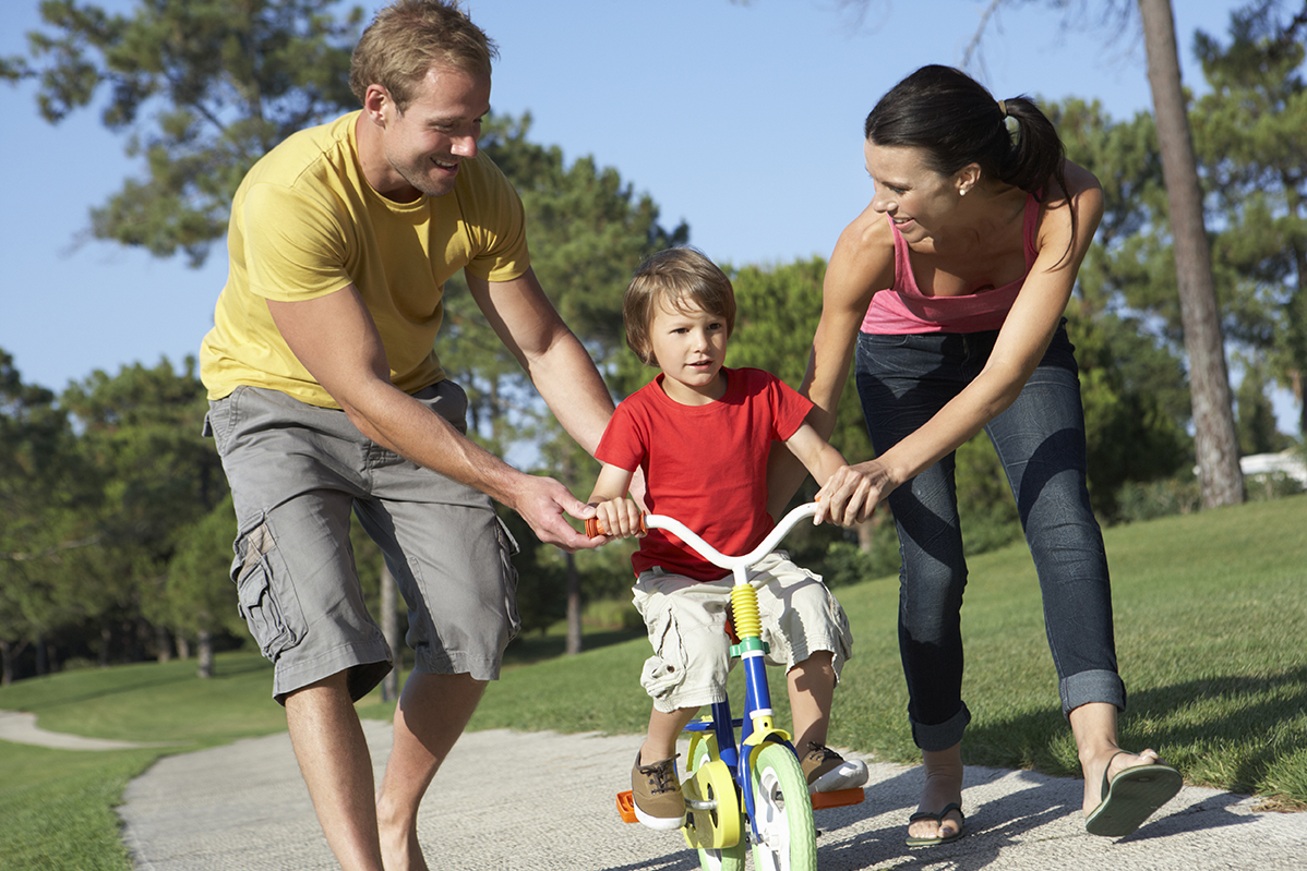 Parents teaching their son to ride a bike in the park